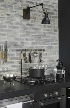 Gray brick in place of a backsplash to contrast the black countertops make for a classic streamlined look. Gray brick in place of a backsplash to contrast the black countertops… Kitchen Interior, Kitchen Inspirations, Grey Kitchens, Industrial House, Brick Kitchen, White Wash Brick, Brick Backsplash, Kitchen Wall Lights, Black Countertops