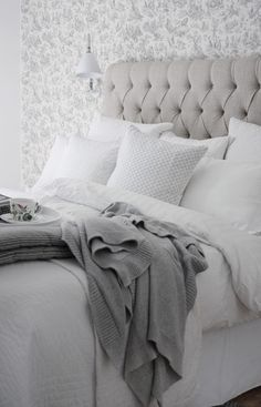 Bedframe + white linen + patterned wall + neutrals