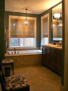 Budget-Friendly Bathroom Makeovers From Rate My Space: After: The homeowners made a good thing even better by simply updating the room's paint, lighting and accessories. The remodeled room with its dark juniper green paint color has an earthy yet refined feel. (Design by Rate My Space contributor tisabellaandm...