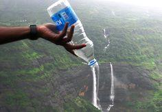 Alguien tira agua de una botella a una cascada