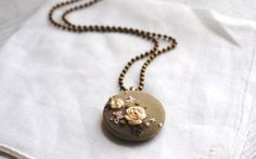 This softly colored necklace features flowers in shades of white and peach on light brown/gold recycled vintage silk repurposed from a ladies blouse. The pendant measures 1 in diameter and hangs from a 19 brass ball chain.  To see my other embroidered pendants, enter my shop section here: https://www.etsy.com/your/shops/stoastn/sections/10656185