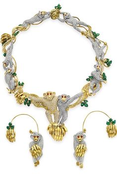 A SUITE OF DIAMOND, EMERALD AND RUBY JEWELRY, BY MASSONI Comprising a necklace, centering upon a pair of pavé-set diamond yellow and white gold monkeys, enhanced by circular-cut ruby eyes, perched atop a bunch of bananas, joined to a series of similarly-set frolicking monkeys,motifs, accented by carved emerald leaves and twisted gold rope, joined to a gold pineapple clasp; and a pair of ear pendants en suite, mounted i n yellow and white gold,Ear pendants signed Massoni $290,500.00
