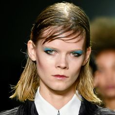 """""""wet look"""" side-swept bangs, and graphic cat eyes accessorized with swipes of neon blue eyeshadow."""