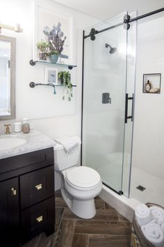 Incorporating lots of white and clear glass helped make the bathroom feel deceptively large and airy. If you have a small bathroom, take my designer's advice and opt for a clear glass door instead of a shower curtain or textured glass door. It instantly opened up more visual square footage, making our bathroom feel much less claustrophobic. The porcelain floor tiles look like reclaimed wood but can withstand tons of humidity and water — laying them in a herringbone pattern adds instant…