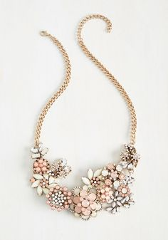 Each time you clasp the golden curb chain of this statement necklace at your nape, you're making a promise to fill the air with flair! Clusters of ivory, pink, and clear gemstones form a garden of glam flowers, turning heads and inspiring awe.