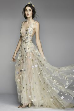 With enchanting, floating golden translucent layers adorned with silver and metallic star appliques, Willowby by Watters's Orion dress is a mesmerizing ode to the starry night sky, perfect for the sultry goddess bride.