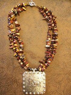 Very pretty multi-colored neutral toned beaded necklace with large praying cowboy concho pendant. $45