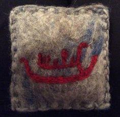 Tovet nålepute med filtet helleristning