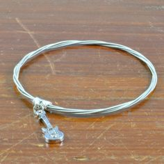 Guitar String Charm Bangle with Guitar Charm from High Strung Studios Guitar String Jewelry Guitar String Bracelet, Studios, Bangle Bracelets, Bangles, Guitar Strings, Charmed, Silver, Gifts, Wire Wrap