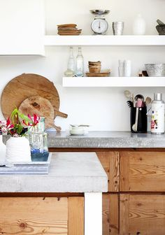 grey concrete counter top wood cabinets and white open shelving