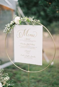 Brides.com: . A simple, but classic menu in elegant gold calligraphy is complemented with a gold ring holder for a modern twist. A white blossom and dash of green plays right from the lush backyard.