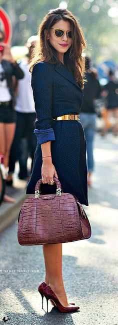Shop this look for $1,075:  http://lookastic.com/women/looks/coat-and-belt-and-tote-bag-and-pumps-and-sunglasses/2818  — Navy Coat  — Gold Belt  — Purple Snake Leather Tote Bag  — Burgundy Snake Leather Pumps  — Gold Sunglasses