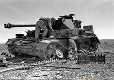 An American soldier examines the tank of the German African corps (Deutsches Afrikakorps) Pz. Kpfw. IV, destroyed during the battle in Tunisia