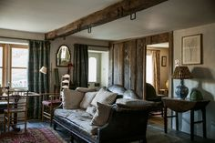 In the living room of Docker Nook, an antique camelback leather sofa piled with understuffed down cushions, late-19th-century William Morris-weave curtains and a floor lamp from Kime's own line. Martin Morrell