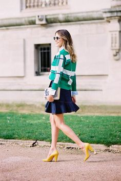 A green plaid cropped jacket is worn with a button-up top, denim skirt and yellow heels.