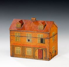 Georgian painted tea caddy in the form of a country house with dormer windows. The lid opens to reveal two lidded compartments.