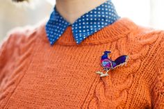 Kittenhood. orange puffed sleeve sweater, blue dotted collar and a swell rooster pin.