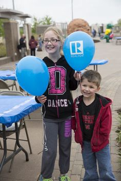 Two kids stop for a quick picture during the REALTORS Care Community Fair. The event, hosted by the REALTORS Association of Lincoln, invited organizations searching for volunteers to set up informational booths and also featured live music, food vendors, and kids activities.