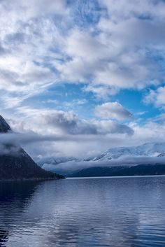 Beautiful view of norwegian fjord - Beautiful view of norwegian fjord, with blue sky and white clouds. Vertical composition