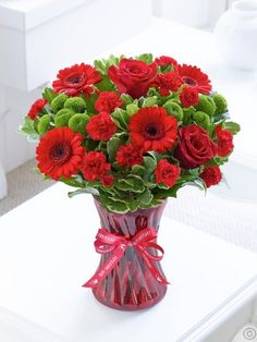 Featuring large-headed red rose, red germinis and red spray carnations with green carnations, green spray chrysanthemums, salal and pittosporum, arranged in a red swirl glass vase and presented in gift packaging. Order Flowers Ireland