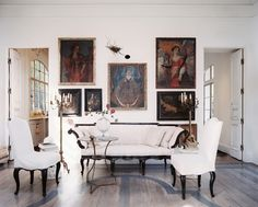 Living Room Photo - A couch and a pair of chairs arranged in front of a wall of paintings
