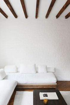 wood beamed ceiling with white brick walls and white sectional sofa. / sfgirlbybay