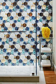 An artistic space displays a wall of colorful shower tiles, with swirling and spiraling shades of blue, green, white, and brown. Design by Staprans Design. #tiledbathroom #greenbathroom #bluebathroom #showertile