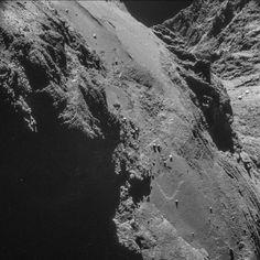 Steile Hänge auf dem  Körper des Kometen. Für die Esa-Forscher sind die Strukturen am rechten Rand viel interessanter. Sie befinden sich auf dem Hals von 67P/Tschuri. Das Material erscheint dort, als sei es zusammengepresst worden. Einer Theorie zufolge könnte der Komet aus der Kollision  von zwei unterschiedlich großen Brocken hervorgegangen sein. Vielleicht ist die Struktur des  Materials am Hals ein Anzeichen dafür?