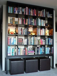 In this IKEA hack from Kramer Design Studio, via Apartment Therapy, a steel frame gives a Expedit a little extra height, and provides a spot to store a little extra seating. 15 Super Smart Ways to Use the IKEA Kallax Bookcase Ikea Bookcase, Built In Bookcase, Bookshelf Bench, Diy Bookcases, Bookshelf Lighting, Kallax Shelf, Ikea Shelves, Shelving Units, Book Shelves