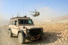 Geländewagen Wolf SSA der Feldjägertruppe auf dem Weg zum Hubschrauberlandeplatz im Feldlager Feyzabad.Im Hintergrund eine CH-53 im Landeanflug.