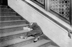 A young newsie asleep on a set of stairs with his papers, in Jersey City, New Jersey, in November of 1912.