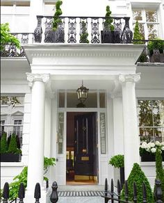 Front stoop with excellent detailing. Ironwork. Carriage lantern. Brass door hardware. Corinthian columns. Formal plantings.