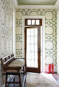 Green geometric wallpaper, vintage turkish rug, red wellies, vintage bench with striped cushion.  Atlanta Homes.
