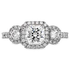 A vintage take on the classic three stone ring. This Hearts On Fire engagement ring features three Hearts On Fire diamonds encircled in pave halos, creating a unique look    Starting at $16,750  Starting Total Carat Weight: 1.65  (includes center diamond of 1.00)  #EngagementRing #Fashion #LoveYou #BrideToBe #Love #TrueLove #MustHave #DreamWedding #WeddingInspiration