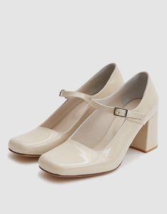 Square toe pumps from Maryam Nassir Zadeh in Beige. Patent calfskin leather upper. Adjustable strap with buckle closure at vamp. Tonal stitching. Lightly padded footbed with embossed logo. Leather lining. Covered block heel with rubber cap.  • Leather u