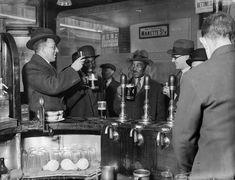 24 November 1933: Men raise their glasses in a public house in London's Soho.(Fox Photos/Getty Images)