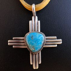 """Natural Morenci Necklace  One of the surest symbols of New Mexico, this is the Zia, which evens graces the state flag. Rendered here is sterling silver, with a handsome center stone of the brightest blue Morenci turquoise, and suspended from rawhide.  Leather strap length- 26"""" Adjustable  Pendant size- 1 ¾"""" x 1 ½""""  Stone size- 13x12mm"""
