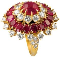 "Van Cleef & Arpels ruby diamond ring.  USA. A fantastic Indian-inspired 18 karat gold, ruby and diamond ring by Van Cleef & Arpels, featuring a center cabochon ruby with an approximate total weight of 3.75 carats, surrounded by 38 diamonds with an approximate total weight of 3.45 carats and 16 rubies of approximately 3.65 carats. Circa 1970's.  Signed, ""Van Cleef & Arpels NY 32651"". Listing via 1stdibs."