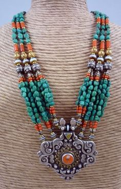 Tibet | Contemporary necklace made from Antique Tibetan elements; sterling silver Tibetan pendant combined with red coral, vermeil beads, dzi agate, turquoise, and brass.