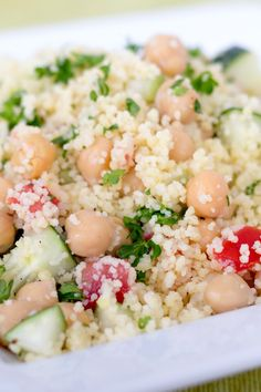 Greek Couscous Recipe with tomato, cucumber, feta cheese, olives, red onion, and chickpeas.