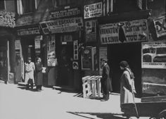 People shopping at small Jewish businesses on a street in the ghetto.  Location:Warsaw, Poland  Date taken:1938  Photographer:John Phillips