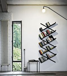 This tilted modern bookshelf with an industrial feel is a great conversation starter for a living room.