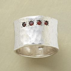 GARNET QUARTET RING -- Nestled in starburst settings, four garnets line up along our wide swath of sterling silver. Exclusive, hand cast with a hammered look. Whole sizes 5 to 9. 1/2W. $148.00