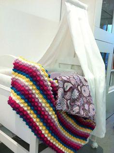 Con este patrón podrás hacer una vistosa manta de colores para el sofá, la cama o una cuna. El punto garbanzo o piña le dará un original acabado.