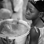 MALI. Dogon region. Songho. Girl with bucket filled with water by the well. 2009.