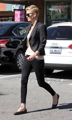 Charlize Theron sticks to her stylish roots in a fitted blazer, jeans and flats.