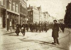 Afbeelding van marcherende militairen (grenadiers) in de Voorstraat te Utrecht, met op de achtergrond de voorgevels van de panden Voorstraat 4 (links) -hoger. 1870-1880