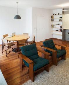 Na sala de estar do apartamento em São Paulo, as duas poltronas PB têm estofado em futon. Para delimitar o estar do jantar, o piso de madeira foi recoberto com um tapete em tom claro. A mesa Bolo de Rolo e as cadeiras Filó compõem a área de refeições.