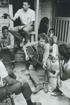 Photographer: Danny Lyon  - Greenwood, Mississippi. 1963. Bob Dylan plays on the back porch of the SNCC office.