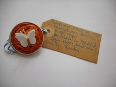 Pillsbury's Pieces No, 172. Pin - metallic bright orange capsule with white paper butterfly. In exchange for a donation to KATHMANDU ANIMAL TREATMENT CENTRE, Nepal. Available at St. George's Church, Madrid on Saturday 13 June from 11.00 - 15.00.